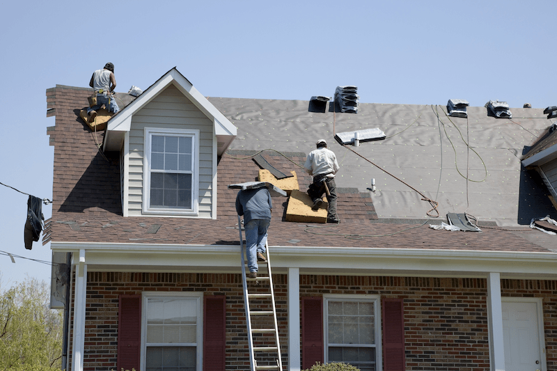 workers replacing roof